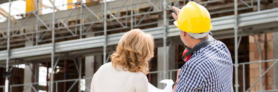 Photo of female customer and male worker pointing at scaffolding and discussing the project