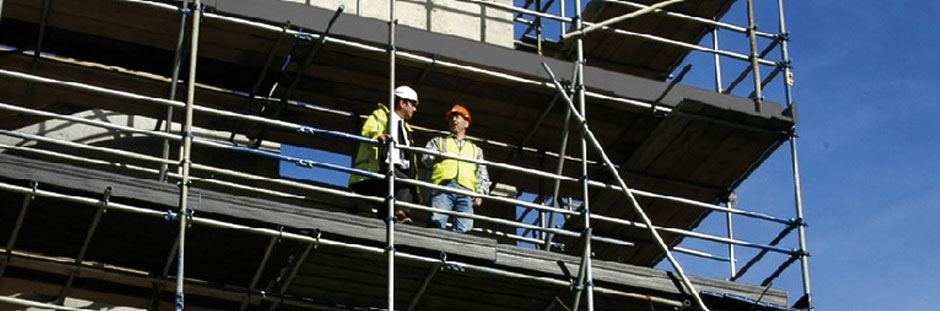Photo of two workers standing on scaffolding that is made using Supadek plastic scaffolding boards.